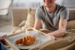 Type gai prenant le petit déjeuner de son amie dans la chambre à coucher images libres de droits
