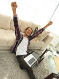 Type heureux avec l'ordinateur portable radieux dans le salon spacieux photos libres de droits