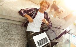 Type heureux avec l'ordinateur portable radieux dans le salon spacieux images libres de droits