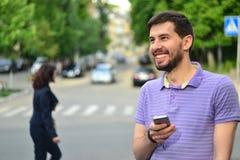 Type heureux avec la transmission de messages de sourire de smartphone dehors Images libres de droits