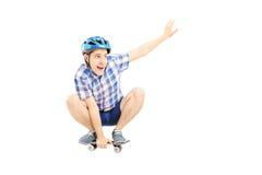 Type heureux avec le casque patinant sur un panneau de patin Photos libres de droits