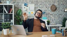 Type heureux dans des écouteurs écoutant la musique au travail ayant le sourire d'amusement clips vidéos