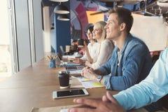 Type heureux et filles jeunes communiquant au travail dans le bureau image stock
