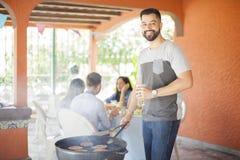 Type heureux faisant cuire des hamburgers dans un gril dehors Photo libre de droits