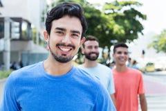 Type hispanique riant marchant avec deux amis dans la ville Photo stock