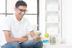 Type indien heureux comptant l'argent Image stock