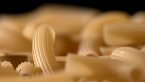 Type of Italian pasta, background, black, rotation. One type of Italian raw, fresh pasta maccheroni, background, on black backgorund, rotation, close up stock video footage