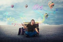 Type joyeux d'étudiant assis détendu sur le plancher écoutant une chanson sur des écouteurs photos stock