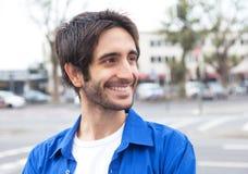 Type latin heureux dans une chemise bleue dans la ville Image libre de droits