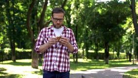 Type mâchant l'hamburger d'aliments de préparation rapide dans la nausée de sentiment de parc, symptôme d'intoxication alimentair photos libres de droits