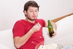 Type mangeant du maïs éclaté et buvant de la bière Photographie stock