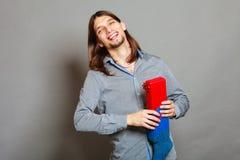 Type mettant le cadeau enveloppé dans la chaussette tricotée de Noël photo libre de droits