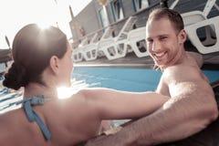 Type millénaire rayonnant souriant dans l'appareil-photo tout en se reposant dans la piscine Photographie stock libre de droits