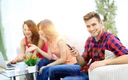 Type moderne avec un smartphone et ses amis s'asseyant sur le couc Images stock