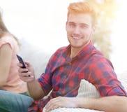 Type moderne avec un smartphone et ses amis s'asseyant sur le couc Photos libres de droits