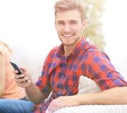 Type moderne avec un smartphone et ses amis s'asseyant sur le couc Images libres de droits