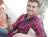 Type moderne avec un smartphone et ses amis s'asseyant sur le divan Images stock