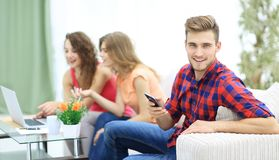 Type moderne avec un smartphone et ses amis s'asseyant sur le divan Photos stock