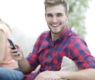 Type moderne avec un smartphone et ses amis s'asseyant sur le divan Photographie stock