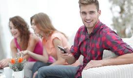 Type moderne avec un smartphone et ses amis s'asseyant sur le divan Photographie stock libre de droits