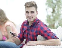 Type moderne avec un smartphone et ses amis s'asseyant sur le divan Image libre de droits