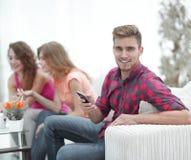 Type moderne avec un smartphone et ses amis s'asseyant sur le divan Images libres de droits