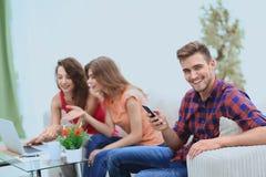 Type moderne avec un smartphone et ses amis s'asseyant sur le divan Photo libre de droits