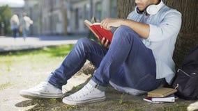 Type multinational s'asseyant sous l'arbre, livre de lecture, amoureux des livres, temps libre clips vidéos