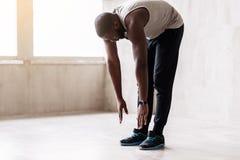 Type musculaire africain calme faisant des exercices d'échauffement Photographie stock libre de droits