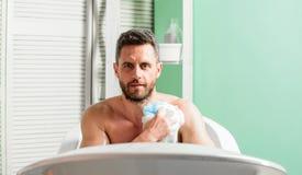 Type musculaire beau d'homme d?tendant dans le bain Routine de choyer et de beaut? Concept de soin de peau Prise du bain avec des photo stock