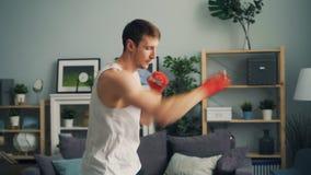 Type musculaire dans la boxe de vêtements de sport seule à l'intérieur en appartement appréciant l'activité clips vidéos