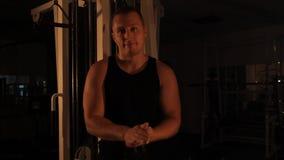 Type musculaire de bodybuilder faisant des exercices Regard dans l'appareil-photo banque de vidéos