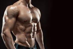 Type musculaire de bodybuilder faisant la pose au-dessus du fond noir Photo stock