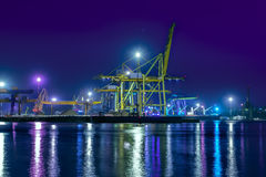 Type of night port. Working freight cranes, a ship at the pier, work in the port. Night photo view of the loading. Beautiful reflection of lights in the sea Stock Image