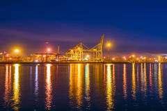 Type of night port. Working freight cranes, a ship at the pier, work in the port. Night photo view of the loading. Beautiful reflection of lights in the sea Stock Photography