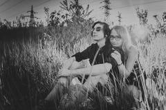Type noir et blanc la fille s'asseyant dans l'herbe Photographie stock