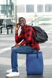 Type noir heureux attendant à la station de train et à l'aide du téléphone portable Images libres de droits