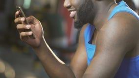 Type noir s'asseyant dans le gymnase et à l'aide du téléphone portable, souriant, mise en réseau sociale clips vidéos