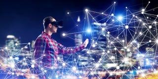 Type portant la chemise vérifiée et le masque virtuel atteignant la main pour sentir sa manière Image stock