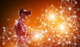 Type portant la chemise vérifiée et le masque virtuel atteignant la main pour sentir sa manière Photos libres de droits