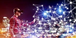 Type portant la chemise vérifiée et le masque virtuel atteignant la main pour sentir sa manière Photo libre de droits