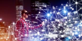 Type portant la chemise vérifiée et le masque virtuel atteignant la main pour sentir sa manière Images libres de droits