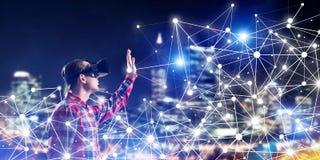Type portant la chemise vérifiée et le masque virtuel atteignant la main pour sentir sa manière Photographie stock libre de droits