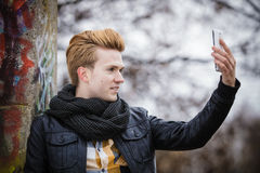 Type prenant la photo d'individu avec le téléphone dehors Images stock