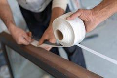 Type protecteur de colle pour deux hommes sur le châssis de fenêtre en bois photo stock