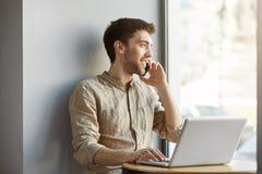 Type rasé attirant joyeux s'asseyant dans l'espace coworking, travaillant sur l'ordinateur portable et parlant au téléphone avec  Photos stock