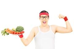 Type ringard tenant le plat avec des légumes et montrant le muscle Photographie stock