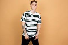 Type roux dans une chemise rayée et supports noirs de jeans sur le fond beige dans le studio photos stock
