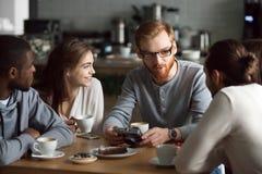 Type roux montrant des photos d'appareil-photo aux amis divers en café Photo libre de droits