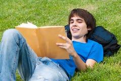 Type s'étendant sur l'herbe et affichant un livre Images stock